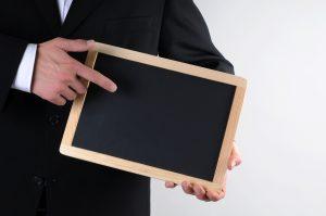 Mann im schwarzen Anzug zeigt auf eine leere schwarze kleine Tafel Thema Und Vieles mehr